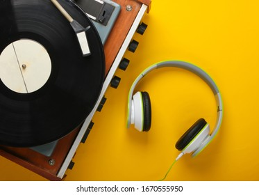 Retro vinyl record player with stereo headphones on yellow background. Top view