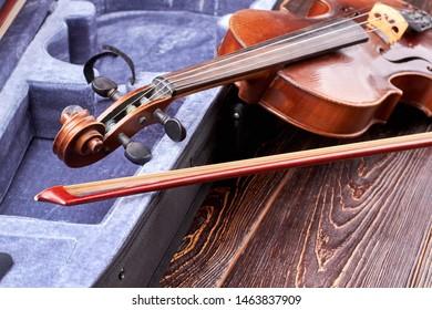 Retro violin on wooden background. Old vintage violin and fiddle stick near velvet case. Musical instrument of orchestra.