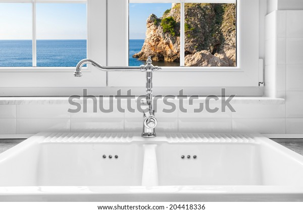 Retro water faucet on new empty white kitchen sink with view on sea rock through the window in background.