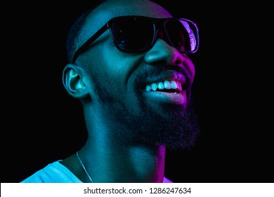 Retro wave portrait of a young happy smiling african man in sunglasses at studio. High Fashion male model in colorful bright lights posing on black background. Art design concept