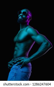 Retro wave portrait of a young naked happy smiling african man in sunglasses at studio. High Fashion male model in colorful bright neon  lights posing on black background. Art design concept
