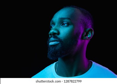 The retro wave or synth wave portrait of a young happy serious african man at studio. High Fashion male model in colorful bright neon lights posing on black background. Art design concept