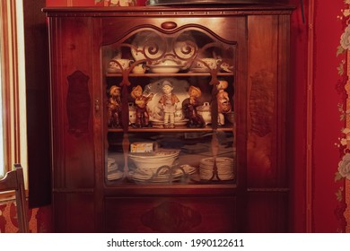 Retro Western dolls in a wooden shelf with antique cutleries, teacups and plates in Toronto, Canada.