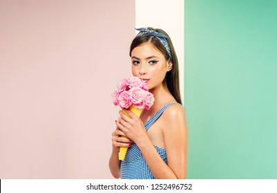 retro woman eating ice cream from flowers. pinup girl with fashion hair. flower bouquet. Florist. Summer. pin up woman with trendy makeup. pretty girl in vintage style, copy space. Effortless beauty.