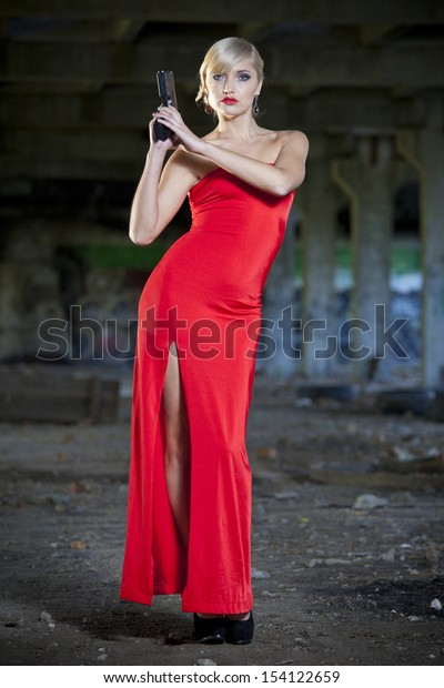 retro woman holding a gun in old fabric ruins