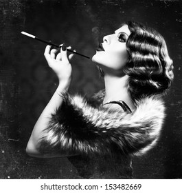 Retro Woman Portrait. Beautiful Woman with Mouthpiece. Cigarette. Smoking Lady. Vintage Styled Black and White Photo. Old Fashioned Makeup and Finger Wave Hairstyle. 20's or 30's style.