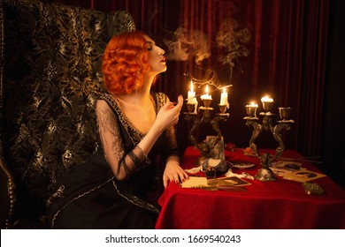 Retro woman with red hair in black vintage dress. Vintage redhead woman with red lips smoking cigarette in mouthpiece. Noir fashion. Candles burn in candlestick. Noir film. Cigarette smoke. 1920s