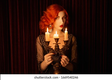 Retro woman with red kinky hair in black vintage dress. Vintage redhead woman with red lips hold candlestick with burning candles. Noir fashion. Candles burn in candlestick. Noir portrait. 1920s