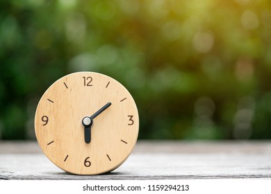 Retro wood clock on wooden table, good morning time concept