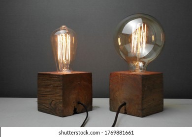 Retro wood lamp with Edison lamp on a gray background.