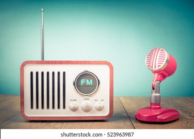 Retro wooden FM radio receiver, old microphone from 60s on table. Vintage style filtered photo