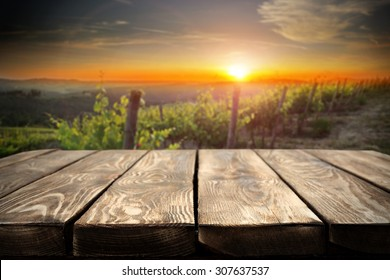 retro wooden table place and green plants of vineyard