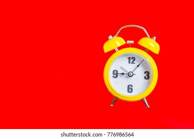 Retro yellow alarm clock with Nine Five Minutes Old Style, Top View on Red Background