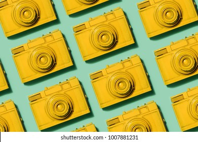 Retro yellow cameras laying in rows on pastel green background. Photography concept.