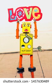 retro yellow robot man holding up a bright and colorful cloth love sign, standing on a old wooden floor
