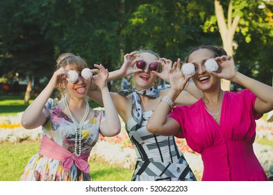 retro-style girls having fun on a summer picnic in a park posing with fruits and sweets