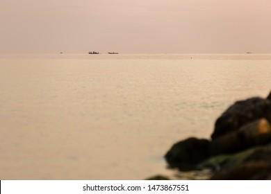 returning fishermen boat silhouette against orange sunrise on Lake Malawi, the sun glitter on the Lake, South-East-Africa
