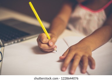 Returning to the school and starting new obligations. Schoolgirl working homework at home. Close up. Copy space. Focus is on hand.
