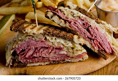 Reuben Sandwich. Classic traditional American sandwich. Pastrami and corned beef on grilled rye bread, melted Swiss cheese, sauerkraut, topped with thousand island dressing served french fries.