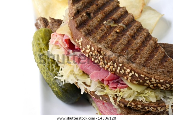 Reuben sandwich on rye bread, with corned beef, sauerkraut and Swiss cheese.  Served with a pickle and potato chips on the side.