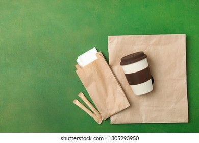 Reusable bamboo glass and craft packages on a green background. Flat lay, copy space. Environmentally friendly materials.