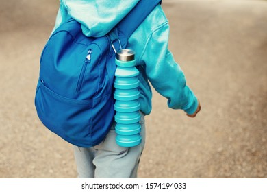 Reusable blue eco friendly water bottle on child's backpack.