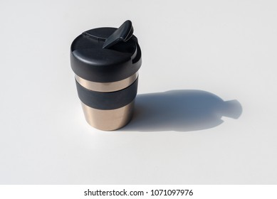 Reusable coffee mug in bright sunlight with harsh shadow on white table