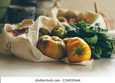 Reusable eco friendly canvas grocery bag with yellow tomatoes and spinach. Local market vegetables. Farmers products. Less plastic. Processed filtered image