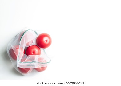 Reusable eco mesh bag with fresh tomatoes on a white background, top view, copy-space. Zero waste and no plastic concept.