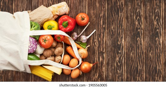 Reusable fabric bag with different groceries on wooden background with copy space.