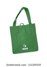 Reusable green shopping bag with recycle symbol isolated on white background