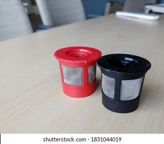 Reusable K cups for coffee machine. Filters are red and black with fine mesh. Individual coffee pods are sitting on a staff room table with chairs out of focus in the background. Selective focus.