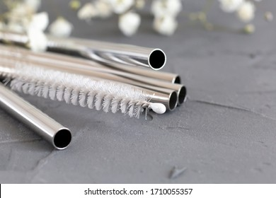 Reusable metal straws for the drinks with a cleaning brush on a gray background. Concept of an eco-friendly lifestyle. Toning. Selective focus.