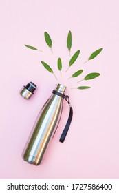 bouteille d'eau en métal réutilisable et feuilles vertes isolées sur fond rose, vue du dessus, aller vert, protection de l'environnement, cesser d'utiliser des bouteilles en plastique, journée mondiale de l'environnement