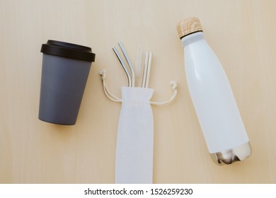 Reusable plastic free and eco friendly utensils. Metal drinking straws, bamboo coffee cup and water bottle, top view. Flat lay. Zero waste and conscious consumption concept. Reduce, reuse, recycle.