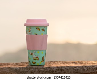 Reusable plastic travel mug tumbler decorated with an all-over print of rainbow coloured unicorn on pastel green background.