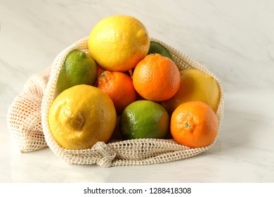 Reusable produce bag filled with fresh citrus fruits. Zero waste concept. Copy space.