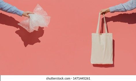 Reusable shopping bag instead of thousands of plastic bags. Eco trend to reduce disposable plastic. Hands on pink background holding plastic bags and cotton shopper bag.