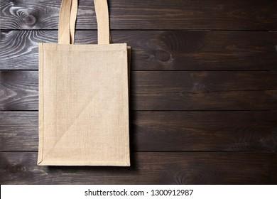 Reusable shopping bag, natural textile fiber, blank eco hessian or jute sack on brown wooden background