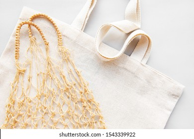 Reusable shopping bags on white background. Ecological concept. Top view of mesh bag and cotton bag. Caring for the environment and the rejection of plastic.