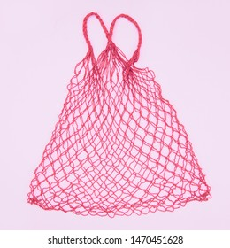 Reusable shopping mesh bag on a pink background. Zero waste, plastic free concept,eco frendly.