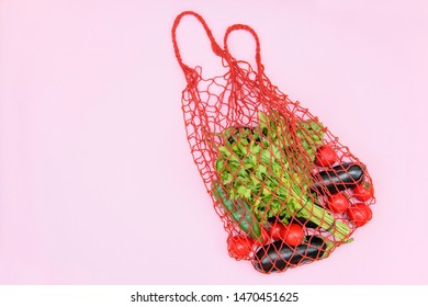 Reusable shopping mesh bag with vegetables on a pink background. Zero waste, plastic free concept,eco frendly.