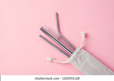 reusable stainless steel straws and cleaning brush in white cotton bag on pink background, eco friendly lifestyle