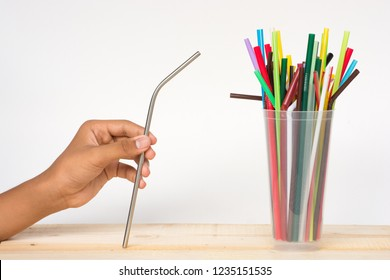 Reusable straw made of stainless steel, held in hand, against single use plastic straw. Beat Plastic Pollution. Say no to plastic. Environmental concept.