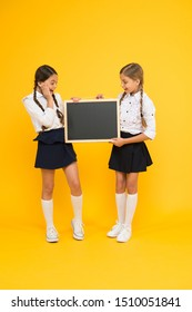 A reusable writing surface. Little children preparing blackboard for lesson. Small pupils with school blackboard. Cute girls holding blackboard on yellow background. Blank blackboard, copy space.