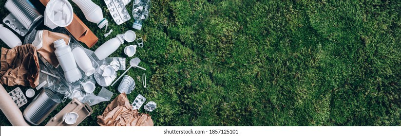 Reuse garbage, recycle, plastic free. Food plastic packaging, trash on green moss background after picnic in forest. Top view. Copy space. Recycling plastic. Environmental pollution, ecology concept