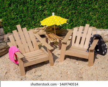 Reused cardboard deck chairs in the sand on a sunny day. Yellow paper umbrella, pink and black towel. Grass background and driftwood. Table made from small tree branches.