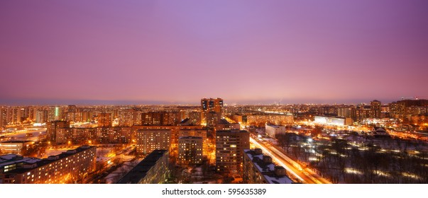 Reutov, Moscow region, Russia. View from the apartment window. Evening. Lamps in the street. Cityscape, view from high. Pink sky panorama