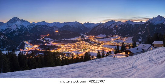 Reutte at night with Duerrenbergalm, snow and mountains in the background, Tyrol, Austria