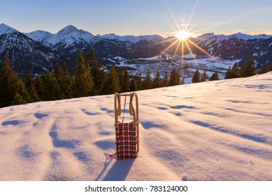 Reutte at sunset with sledge, snow and mountains in the background, Tyrol, Austria